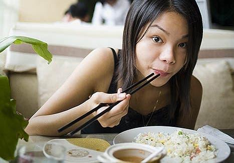 Asiática comiendo arroz